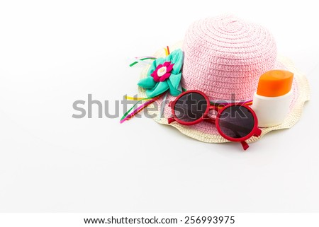 Pink woven hat with body lotion and red sunglasses on white background. - stock photo