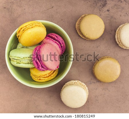 pink, yellow and green macaroons on old brown table  - stock photo