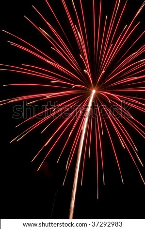 Pinkish burst of fireworks with long white rocket trail and white tips