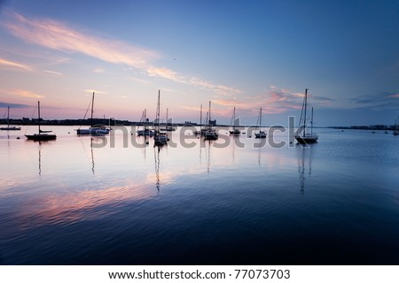 Pinks and blues of sunrise sky over boats in Boston Harbor - stock photo