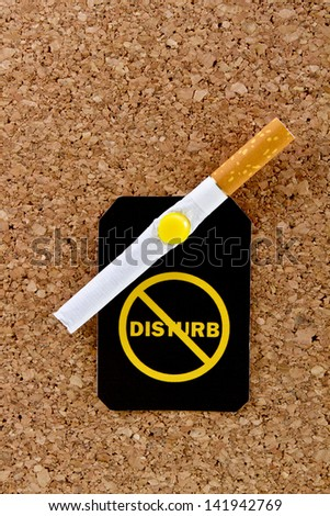 Pinned to a cork board filter cigarette with a yellow do not disturb label.Stop smoking concept. - stock photo