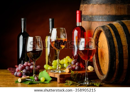 pinot gris, Cabernet sauvignon and pino noir in cellar with barrels - stock photo