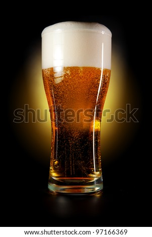 Pint glass of beer amber color with head on a black background. Isolated path included. - stock photo