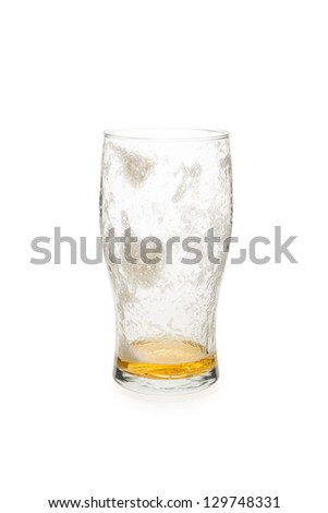 Pint glass with just a little beer in the bottom of the glass. - stock photo
