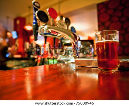 Pint of beer on a bar in a traditional style English pub - stock photo
