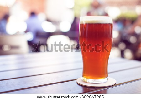 Pint of crafted ale on wooden table in beer garden - stock photo