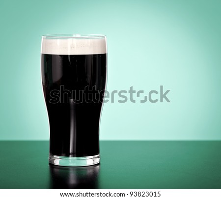 Pint of Irish stout beer on a green background - stock photo