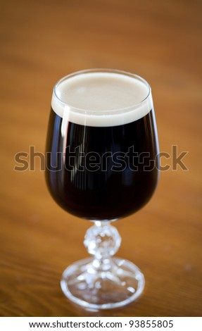 Pint of Irish stout beer on a table background - stock photo