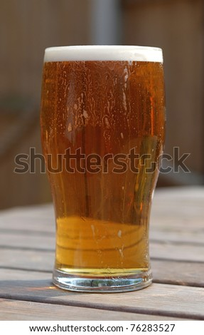 Pint of refreshing ale on table in pub beer garden table - stock photo