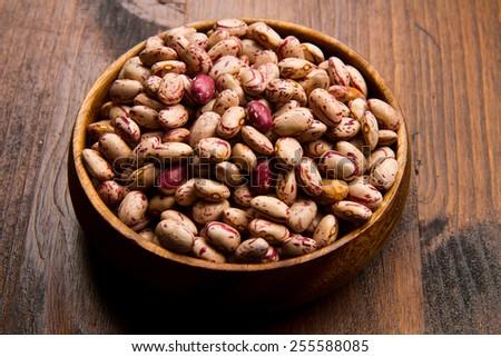 pinto beans on wood bowl - stock photo