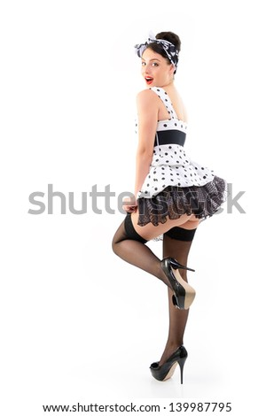 Pinup girl on high heels in spotted dress stocking, full length portrait of seductive young happy sexy woman in pin-up style, over white - stock photo