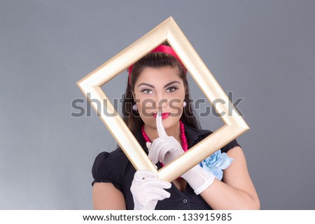 pinup girl with a frame around her face and finger on lips over grey - stock photo