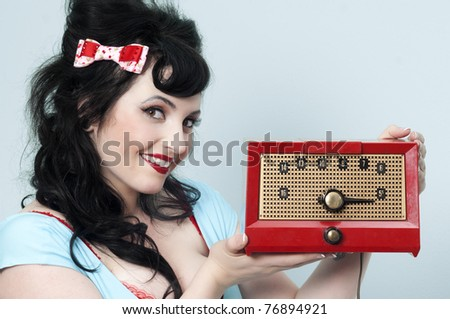 Pinup model holding a red vintage radio