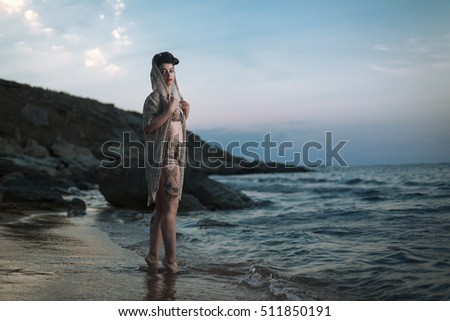Pinup model in the swimsuit with make up and hairstyle on the beach. Beautiful and sexy woman standing into the water on the sea. Relaxing vacation time.