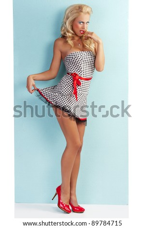 pinup style portrait of a beautiful and sexy blond girl wearing a very short dress black and white with red belt and blue eye makeup - stock photo