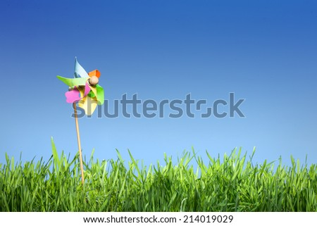 Pinwheel on the grass under the blue sky - stock photo