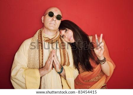 Pious guru prays with woman makes peace symbol - stock photo