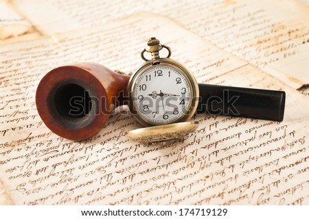 pipe and pocketwatch on letters background - stock photo