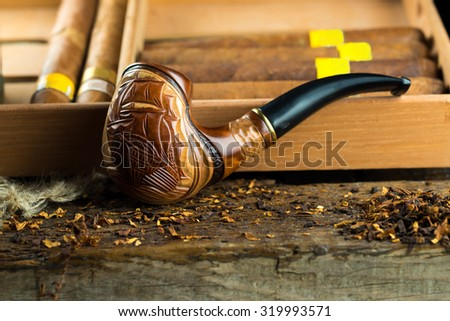 Pipe is close to cigars - stock photo