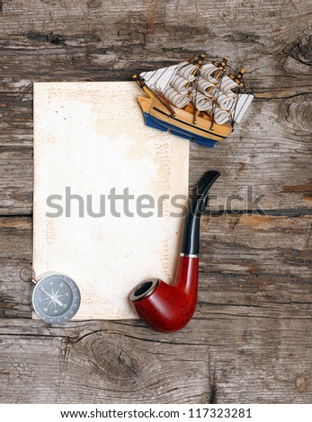 pipe, old paper, compass and model classic boat on wood background - stock photo