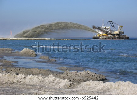 Pipe pushing sand onto the beach - stock photo