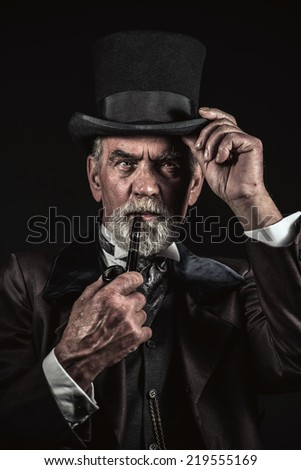 Pipe smoking vintage victorian man with black hat and gray hair and beard. Studio shot against dark background. - stock photo