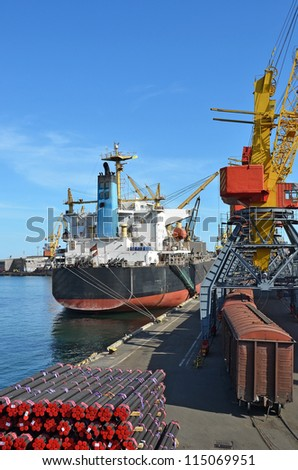 Pipe stack, ship ans train under crane bridge - stock photo