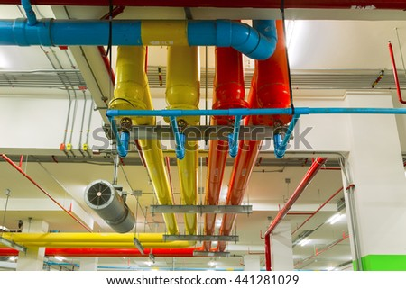 Pipe systems, pipeline extinguishing water on industrial building ceiling. - stock photo