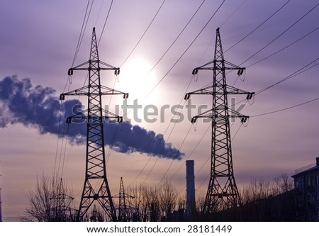 Pipe with smoke and line of electricity transmission on background of city