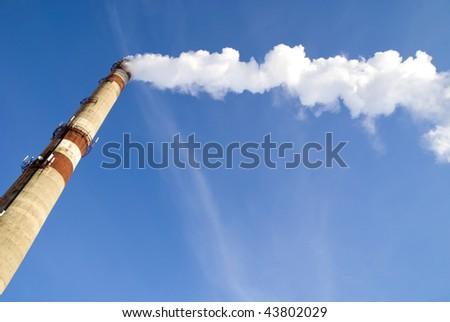 pipe with smoke on blue sky - stock photo