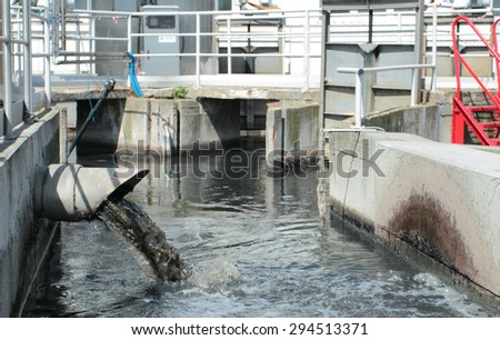 Pipe with wastewater in treatment plant - stock photo