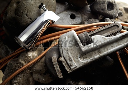 Pipe Wrench and Copper Pipe and Faucet with on Wet Rock
