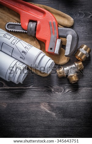Pipe wrench brass plumbing fittings protective gloves blueprint rolls. - stock photo