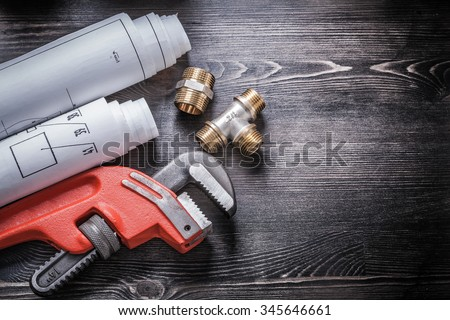 Pipe wrench copper plumbing fixtures rolled up construction drawings. - stock photo