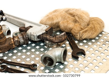 Pipe wrench, pipe connections, wrenches, water tap and flax on a metal grating - stock photo