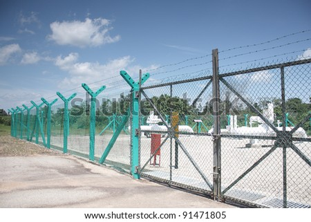 Pipeline block valve station. White above ground pipe and green fence. - stock photo
