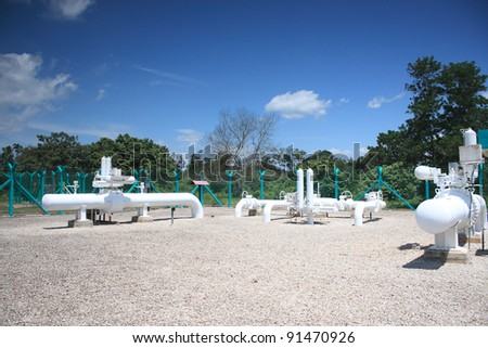 Pipeline block valve station. White above ground pipe and green fence. gravel foreground. - stock photo