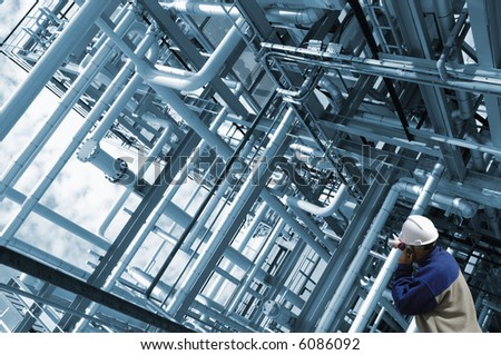 pipeline construction being examined by engineer, pipelines in a blue metallic toning idea - stock photo