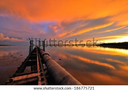 Pipeline during burning sunset at Serasa Beach, Brunei - stock photo