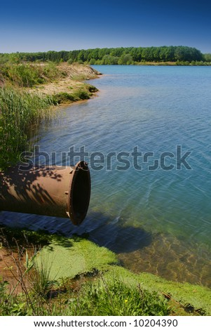 Pipeline ends in beautiful blue lake. - stock photo