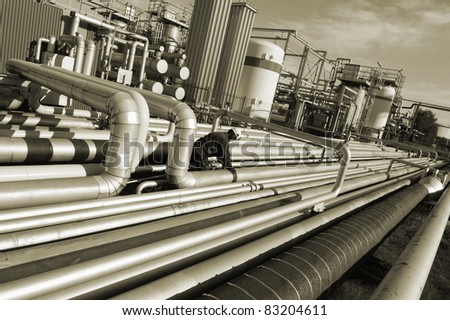pipelines inside oil refinery, worker climbing on pipes, brown toning idea - stock photo