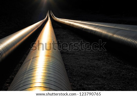 Pipelines reflecting the evening light, disappearing into darkness - stock photo