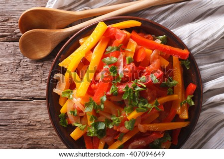 Piperade: peppers with tomatoes and onions close up on a plate. horizontal view from above