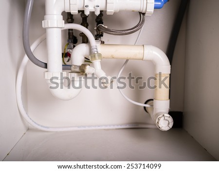 Pipes and plumbing under a kitchen sink - stock photo