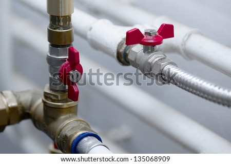 Pipes and valves of a heating system - stock photo