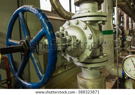 Pipes and valves with blue knobs for hot water - stock photo