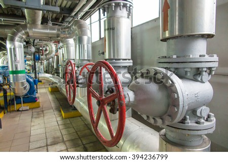Pipes and valves with red knobs for hot water - stock photo