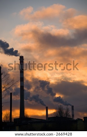 Pipes of factories on a background of a sunset in industrial area of St.-Petersburg