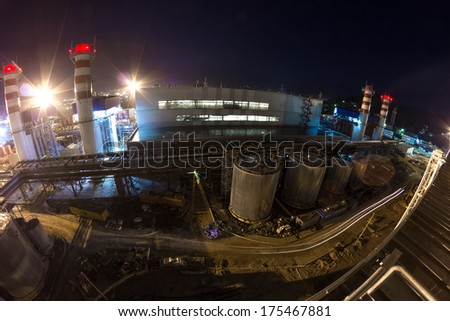 pipes of thermal power plant and and city in the evening - stock photo