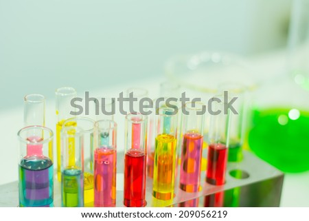 Pipette adding fluid to one of several test tubes  - stock photo
